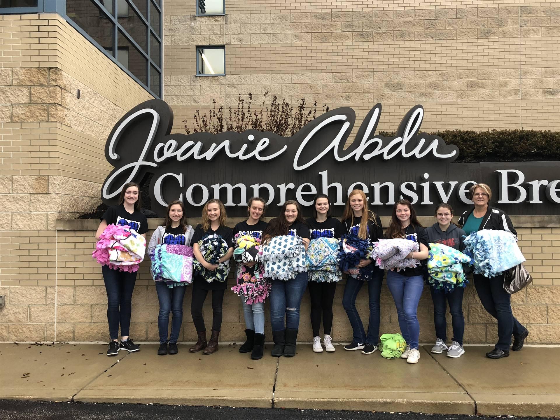 High school cheerleaders and Mrs. Denovchek delivering handmade blankets to cancer patients